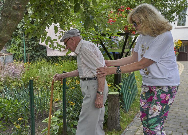 starszy pan w ogrodzie idzie o lasce korzystając z opieki kobiety