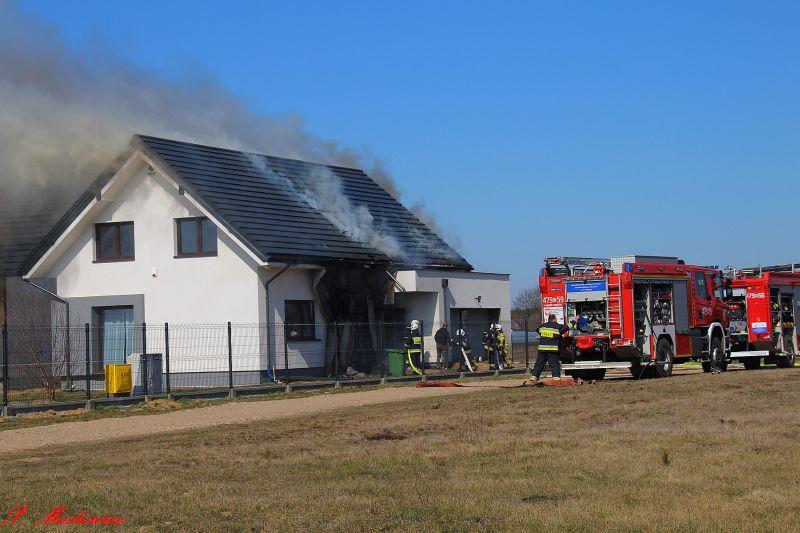 Płonący dach domu gaszą strażacy