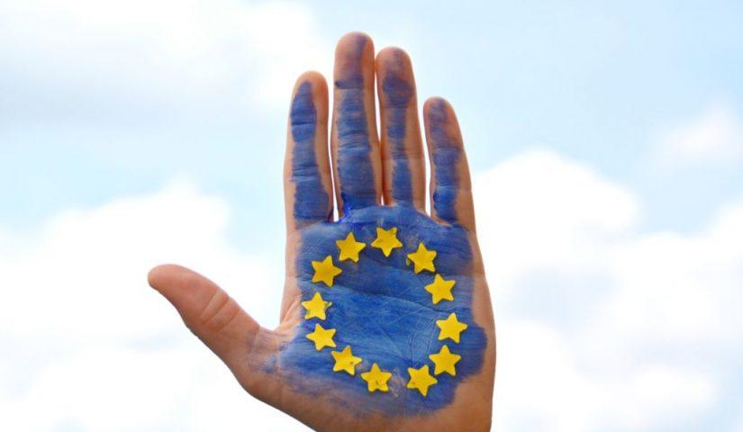 Pomalowana na niebiesko ręka z żółtymi gwiazdkami - symbol Unii Europejskiej