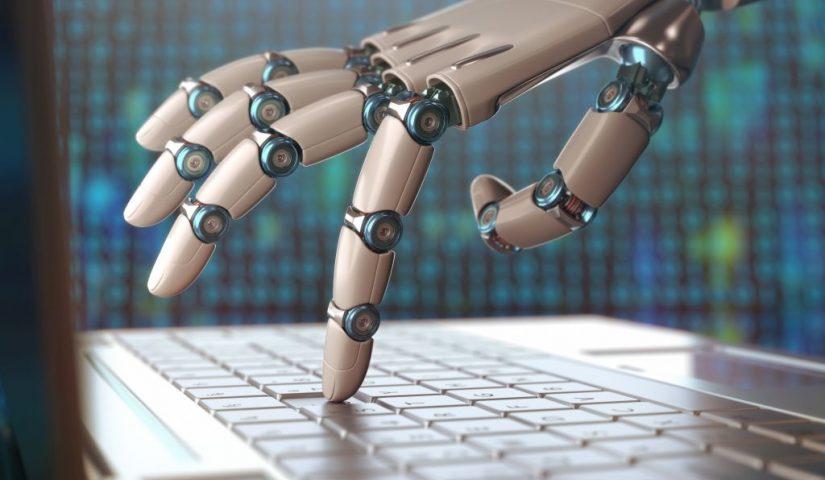Ręka robota naciska klawiaturę laptopa