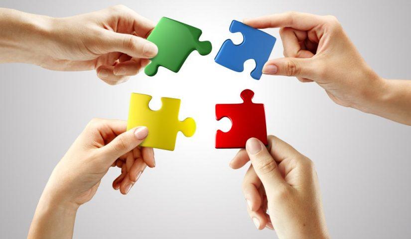 Cztery dłonie trzymają blisko siebie cztery kolorowe puzzle